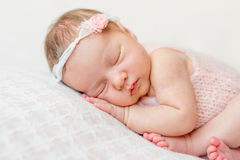 Sweet face of a newborn girl. With headband and flower on head sleeping on hand, close up Stock Photos