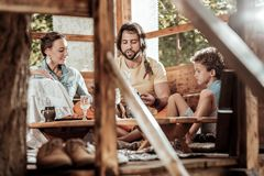 Sweet family of hippies having lunch at garden house