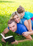Sweet family reading a book on the green grass Royalty Free Stock Images