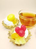 Sweet fancy cakes with fruits and tea Royalty Free Stock Photography