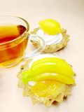 Sweet fancy cakes with fruits and tea Stock Image