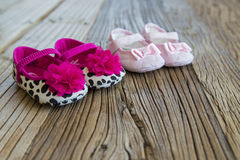 Sweet fancy and colorful baby shoes on the wooden table. Two pairs of sweet fancy and colorful adorable baby shoes on the wooden table Stock Images