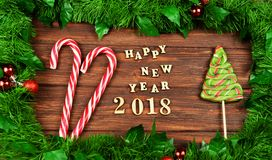 Sweet festive ladies, candy in the form of a staff Santa Claus. And a Christmas tree with the text of a happy new year 2018 in a frame of a Christmas tree with Royalty Free Stock Photo