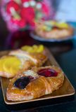 Sweet flaky pastry with fruits. Sweet flaky pastry with mango and cherry jam royalty free stock images
