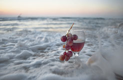 The Sweet Foam. The glass of wine and grapes in the waves of the Mediterranean sea Stock Photos