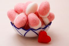 Pink jellies or marshmallows with sugar in bowl royalty free stock photography
