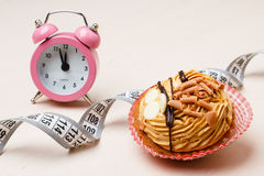 Sweet food measuring tape and clock on table Royalty Free Stock Photography
