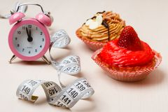 Sweet food measuring tape and clock on table Royalty Free Stock Photos