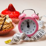 Sweet food measuring tape and clock on table Stock Photo