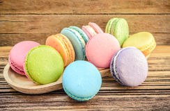 Sweet French macaroon dessert on wood plate. Colorful sweet French macaroon dessert on wood plate Royalty Free Stock Photos