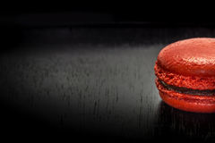 Sweet french macaroon or macaron on black wooden table. Space fo Stock Image