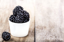 Sweet Fresh  Blackberries in a white bowl. On  bright wooden background close up with copy space Stock Photos