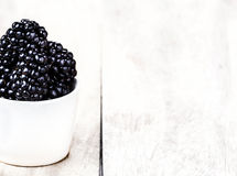 Sweet Fresh  Blackberries in a white bowl. On  bright wooden background close up with copy space Stock Image