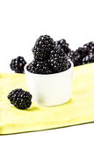 Sweet Fresh  Blackberries in a white bowl. On a yellow napkin isolated on white background, closeup Stock Image