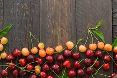 Sweet fresh cherries background. Scattered cherries on blue rustic wood pattern with copy space. Cherry fruit backround. Garden fr. Sweet fresh cherries stock images