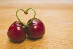 Sweet fresh cherries in film style with pies heart-shaped. Stock Photo