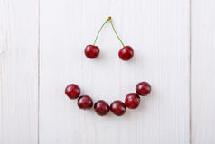 Sweet fresh cherries smile on white wood background. Smiley face from sweet fresh cherries. Smile sign from healthy food. Fruits closeup on white rustic wood royalty free stock images