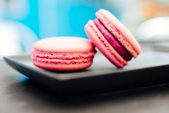 Sweet, fresh macarons with coffee in a blue cup on a black table stock photos