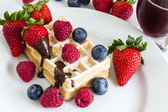 Sweet fresh mixed fruits with tasty waffles and red juice. Ripe berry of raspberries, strawberries and blueberries, some of on a waffle and behind white plate Royalty Free Stock Photos