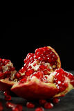 The sweet, fresh and natural garnet for desserts and beverages on a black background. Bright red pomegranate broke down Stock Image