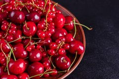 Sweet fresh organic cherry background close-up. Cherry in the plate with leaves on a dark background royalty free stock photography