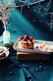 Sweet fresh poppy seed pancakes with chocolate fondant and decorated with fresh raspberries on a wooden board on a kitchen table w Stock Photo