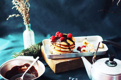 Sweet fresh poppy seed pancakes with chocolate fondant and decorated with fresh raspberries on a wooden board on a kitchen table w Royalty Free Stock Photo