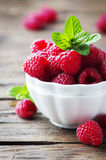 Sweet fresh raspberry and mint on the wooden table. Selective focus Royalty Free Stock Photo