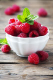 Sweet fresh raspberry and mint on the wooden table. Selective focus Stock Images