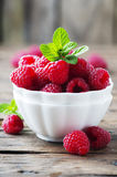Sweet fresh raspberry and mint on the wooden table. Selective focus Royalty Free Stock Images