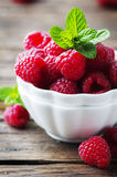 Sweet fresh raspberry and mint on the wooden table. Selective focus Stock Photography