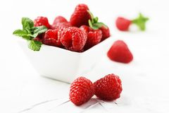 Sweet fresh raspberry on the white stone background. Selective focus Royalty Free Stock Image