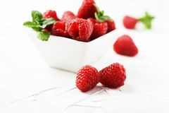 Sweet fresh raspberry on the white stone background. Selective focus Stock Photo