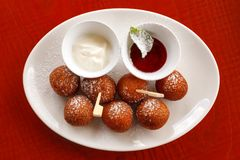 Sweet fried round balls doughnuts sprinkled with sugar powder on a white plate with sour cream and jam. Pastry and desserts. Soft focus, selective focus royalty free stock images