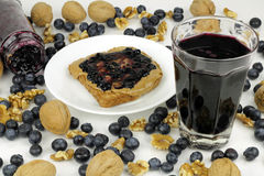 Sweet Fruit Nut Treats. Blueberry preserves in jar on side and on almond butter on toast, blueberry juice, whole and shelled walnuts. Whole blueberries Royalty Free Stock Photo