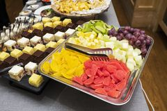 Sweet fruit slices spread out on a metal tray. Sweet fruit slices, watermelon, melon, grapes, kiwi, banana and candied fruits spread out on a metal tray stock photos