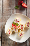 Sweet Fruit Sushi Roll. Dessert Sushi - Roll with Various Fruit and Cream inside. Pancake outside. Served with Strawberrie stock photo