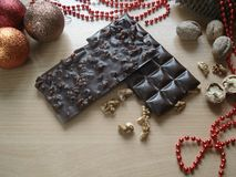 Sweet gift for the New Year. Christmas decorations. Chocolate with walnuts. Royalty Free Stock Images