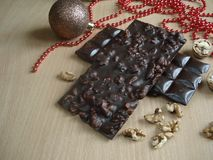 Sweet gift for the New Year. Christmas decorations. Chocolate with walnuts. Royalty Free Stock Photo
