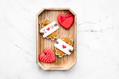 Sweet gift for St Valentine`s Day. Heart shaped gingerbread in tray on light grey background top view copy space. Sweet gift for St Valentine`s Day. Heart shaped Stock Photo