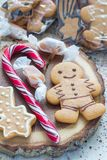 Sweet gifts for holiydays. Homemade christmas gingerbread cookies and caramel candies on wooden board, vertical. Sweet gifts for holiydays. Homemade christmas royalty free stock image