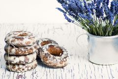 Sweet gingerbread cookies in white glaze, in an aluminum mug a bouquet of lavender flowers.  royalty free stock image