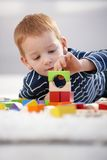 Sweet gingerish boy building tower at home Stock Photos