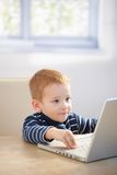 Sweet gingerish kid playing video game on laptop Royalty Free Stock Photography