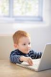 Sweet gingerish kid playing video game on laptop. At home, smiling Royalty Free Stock Photography