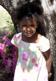 Sweet Girl. A beutiful young african american girl stands against a tree Royalty Free Stock Image