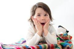 Sweet girl amazed sit on colored blanket isolated on white backg Stock Photos