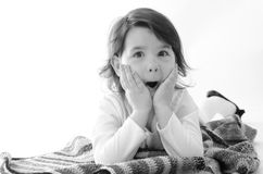 Sweet girl amazed sit on colored blanket isolated on white backg Stock Images