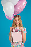 Sweet girl with baloons and little prersents bag in the hands on the blue background. Stock Photos