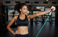 Sweet girl with a beautiful figure  working out with resistance expander in gym Stock Images